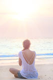 Woman practicing yoga at sunrise beach. Young caucasian woman practicing yoga at sunrise beach Stock Images