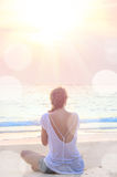 Woman practicing yoga at sunrise beach. Young caucasian woman practicing yoga at sunrise beach Royalty Free Stock Photos