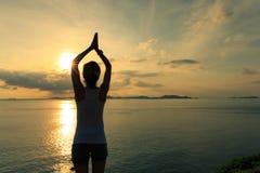Woman practicing yoga at sunrise seaside Stock Image