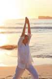Woman practicing yoga during the sunset Stock Photos