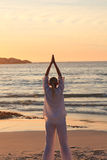 Woman practicing yoga during the sunset Royalty Free Stock Image