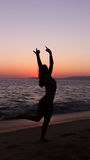 Woman practicing Yoga, sunset in the beach Royalty Free Stock Image