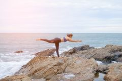 The woman practicing yoga sunset on the beach. Stock Images