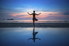 Woman practicing yoga during sunset at seaside. Stock Photography