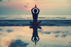Woman practicing yoga during sunset at the seaside. Stock Photos