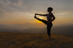 silhouette of a young women practising yoga during Royalty Free Stock Photo