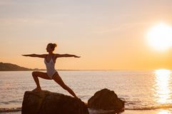 Woman is practicing yoga at sunset on stone. Silhouette of yoga woman on the beach at sunset. Calm and self control stock photo