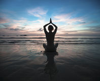 Woman practicing yoga during surrealistic sunset at the seaside. Stock Photo
