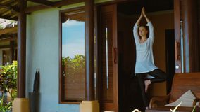 Woman is practicing yoga in tree position, meditating and stretches, on the porch of bungalow on the beach in Bali, nature sounds. Woman is practicing yoga in stock video