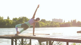 Woman practicing yoga on wooden bridge of river. stock video