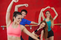 Woman Practicing Zumba With Friends. Happy young women practicing Zumba with friends in gym Royalty Free Stock Image