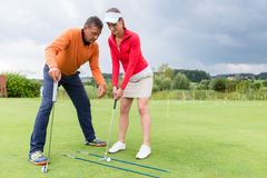 Woman practising with golf trainer. Golf trainer working with female golf player on driving range stock image