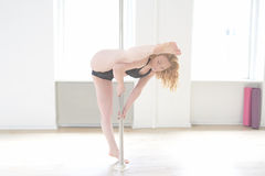 Woman practising pole dance in a pole fitness cl Royalty Free Stock Photos