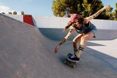 Woman practising skateboarding at skate park. Skater female rides on skateboard at skate park ramp. Young woman practising skateboarding outdoors at skate park Stock Images