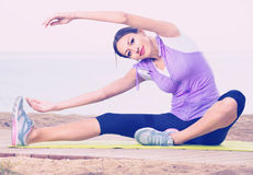 Woman practising yoga poses sitting on beach by sea Stock Photography