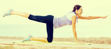 Woman practising yoga poses standing on beach Stock Images