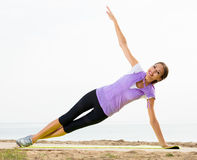 Woman practising yoga poses standing on beach Royalty Free Stock Images