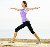 Woman practising yoga poses standing on beach Royalty Free Stock Photos