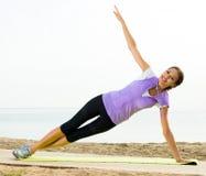 Woman practising yoga poses standing on beach Royalty Free Stock Photo