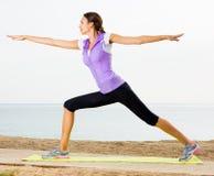 Woman practising yoga poses standing on beach Stock Photos
