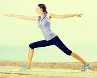 Woman practising yoga poses standing on beach Royalty Free Stock Image