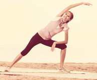 Woman practising yoga poses standing on beach Royalty Free Stock Photography