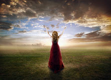 Woman praising. Woman lifting up her hands at sunset Royalty Free Stock Image