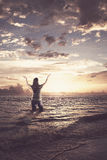 Woman praising in the ocean. Woman standing in the ocean and lifting her arms up in praise Royalty Free Stock Images