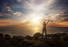 Woman praising at sunrise. A woman standing at the ocean with her arms lifted in praise Stock Photos