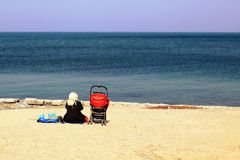 A woman with a pram looking at the sea Royalty Free Stock Image