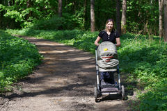 Woman with a pram for a walk Stock Photos