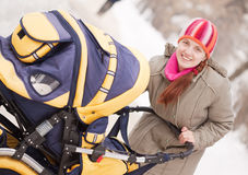 Woman with pram in winter Stock Photos