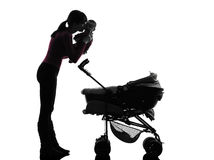 Woman prams holding kissing baby silhouette. One caucasian women prams holding baby kissing silhouette on white background Royalty Free Stock Photo