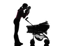 Woman prams holding kissing baby silhouette Royalty Free Stock Image