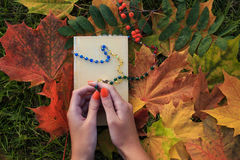 Woman pray to god with colour beaded rosary. She is lying on the ground with autumn leaves Stock Photo