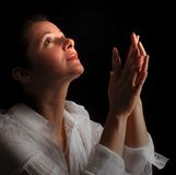Woman in prayer. Woman with hands folded in prayer, looking up toward the Light Stock Photo