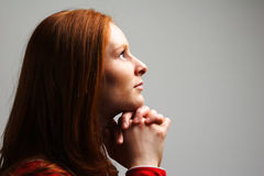 Woman in Prayer. A young woman praying to God in dramatic lighting and on plain background Stock Photo