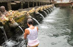 Woman in prayer in holy water at Pura Tirta Empul, hindu temple Royalty Free Stock Photo