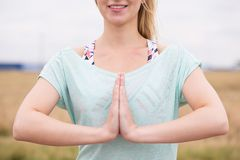 Woman in prayer pose. Calm and peaceful woman standing in prayer pose royalty free stock photography