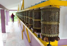 Woman and prayer wheels in a row Royalty Free Stock Photo