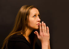 Woman praying. On a dark background Stock Images