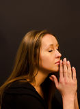 Woman praying. On a dark background Stock Photo