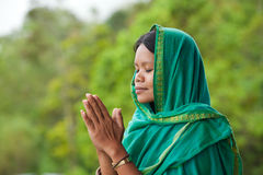 Woman praying. Young south-east asian woman praying with head dress Royalty Free Stock Photo