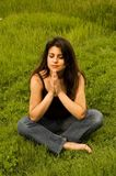 Woman praying. An attractive woman alone in a field of lush green grass praying royalty free stock photography