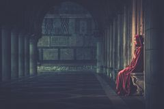 Woman praying alone. Woman in red cloak praying alone Stock Photography
