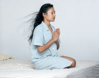 Woman praying in bed Stock Photography