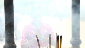 Woman praying behind smoke from burning sticks stock footage