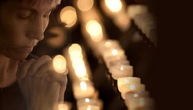 Woman praying in Catholic church. With candles Stock Photos