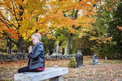 Woman praying in cemetery. A side view of an elderly woman sitting on a bench praying in a cemetery royalty free stock image