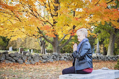 Woman praying in cemetery Royalty Free Stock Images